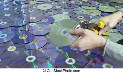 Woman destroying CD and DVD discs