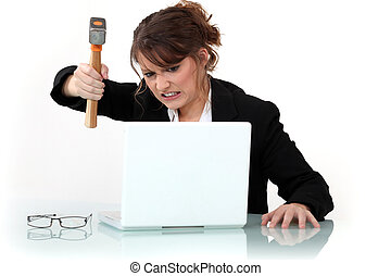 woman destroying laptop with hammer