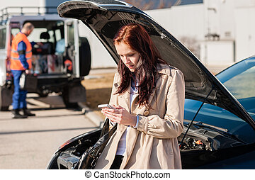 Woman dialing her phone after car breakdown