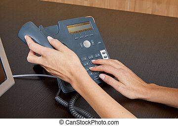 Woman dialing on a telephone
