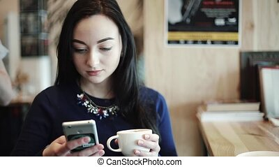 Woman Dials text in a smartphone searches for information on the Internet reads looks at photos