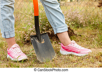 Woman digging hole in garden