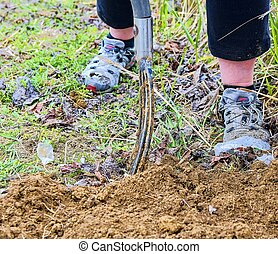 Woman digging soil with garden fork. Gardening and hobby concept. Gardening in the spring