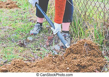 Woman digging soil with garden fork. Gardening and hobby concept