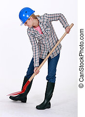 Woman digging with a shovel