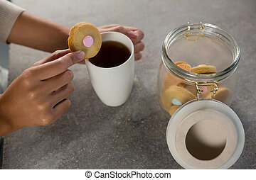 Woman dipping a cookie into black coffee