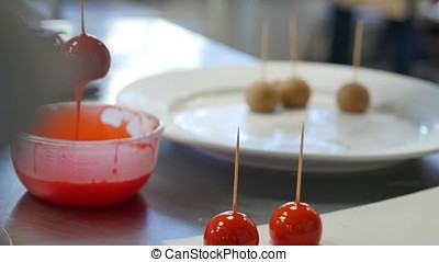 Woman dipping candy apple into bowl with caramel.
