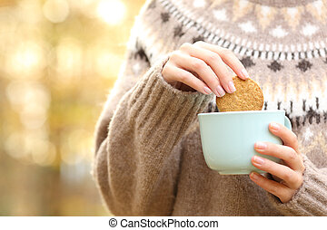 Woman dipping cookie in a coffee mug in autumn