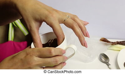 Woman dipping dark chocolate biscuit cookies.