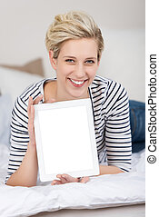 Woman Displaying Digital Tablet While Lying On Bed