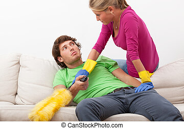 Woman disturbing her husband in watching tv