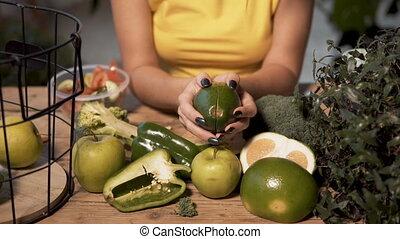 Woman Divides Avocado - Woman dividing an avocado in half at...