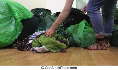 Woman divides her clothes into plastic bags