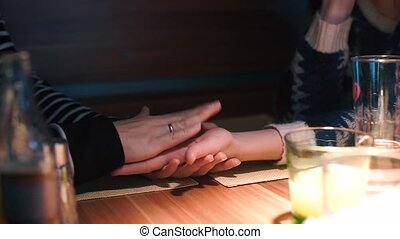 Woman divines on the hand of a lesbian friend at a table in a restaurant.