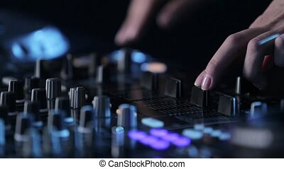 Woman dj play electronic music on mixing console in nightclub, hands of girl dj, fingers with rings click on buttons that glow with different colors and twist vinyl, dark background