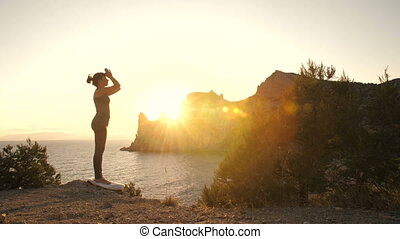Woman do yoga at sunset near ocean
