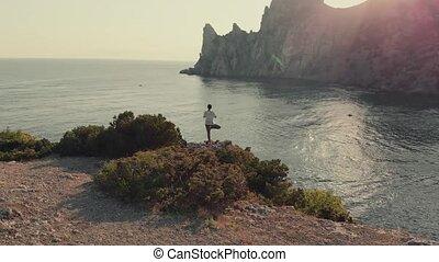 Woman do yoga at sunset
