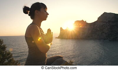 Woman do yoga at sunset