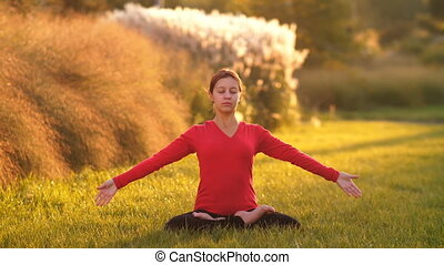 Woman do yoga on the grass
