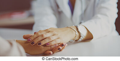 Woman doctor helping senior holding hand in hospital
