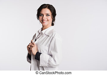 Woman doctor holding up her collar and standing against a white background