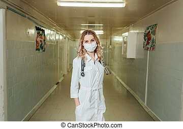 woman doctor in a white coat in the corridor