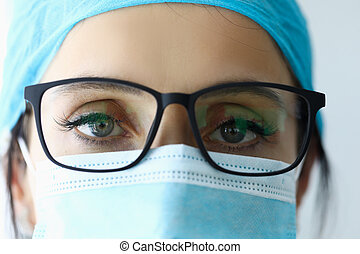 Woman doctor in glasses and medical mask portrait.
