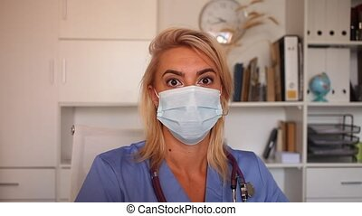 Woman doctor in protective mask posing in the office of the clinic