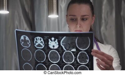 Woman doctor is watching x-ray of brain while sitting at table in clinic.