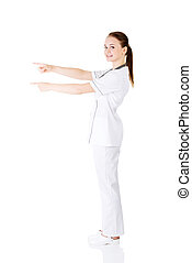 Woman doctor or nurse pointing on copy space.