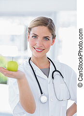 Woman doctor showing an apple
