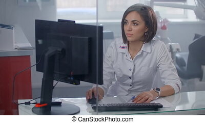 Woman doctor sitting at desk working on laptop computer.