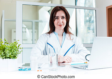 Woman doctor sitting at the table