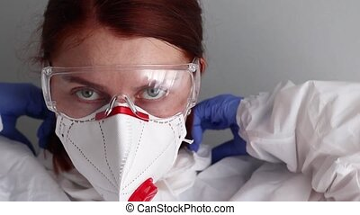 A woman doctor wears goggles, a mask and protective clothing for protection against the virus epidemic coronavirus