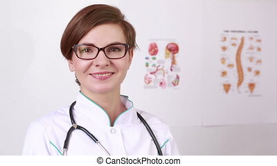 woman doctor with a stethoscope takes off his glasses. smiling at the camera