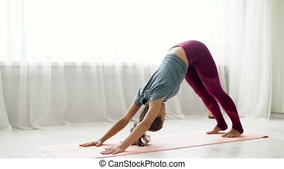 woman does downward-facing dog pose at yoga studio -...