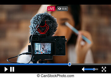 Woman does makeup while recording live stream with vide player interface