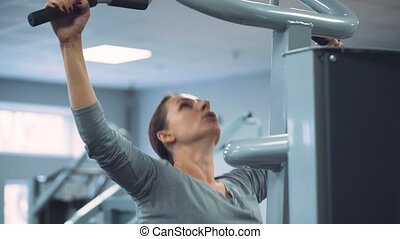 Woman does pull-ups on gravitron for strengthening the shoulder muscles in the gym