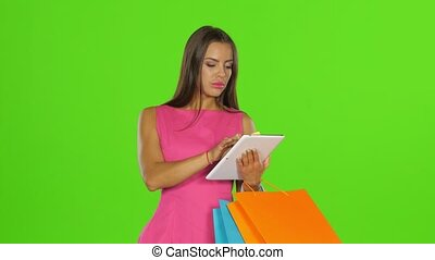Woman does shopping with credit card and tablet. Green screen. Close up