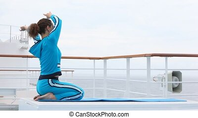 woman does waves by hands in air, sitting on lap, on ship deck