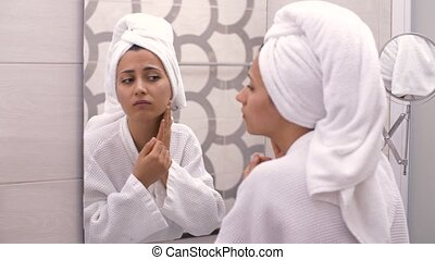 Woman having a bad day grimacing in disgust as she looks in the mirror