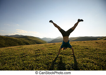 woman doing a handstand in a meadow