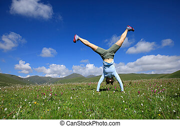 woman doing a handstand in a mountain peak meadow