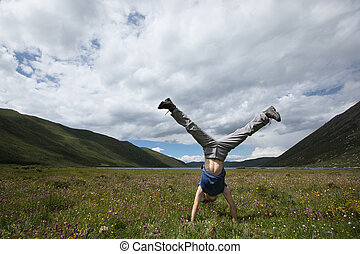 woman doing a handstand on mountain meadow