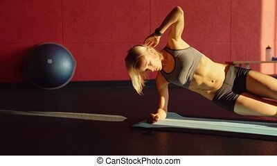 Woman doing a Side plank for abdominal workout on blue mat. This Video about fitness.