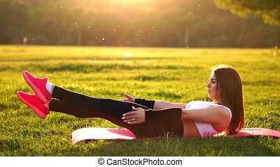 Woman doing abdominal crunches exercise on the fitness mat in summer park In slow motion at sunset.