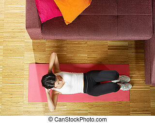 woman doing abs exercise at home - mid adult woman training...