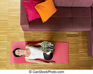 woman doing abs exercise at home - mid adult woman with legs...