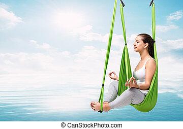 Woman doing aerial antigravity yoga over lake.