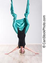 Woman doing aerial yoga upside down on head